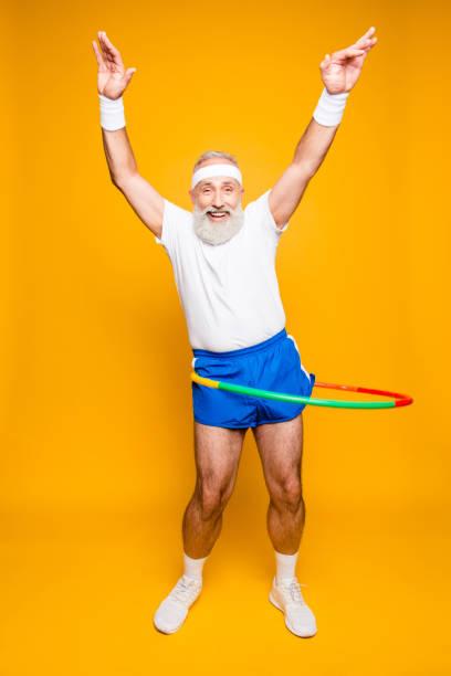 emotionale kühle fröhlich begeistert verrückte lustige täuschen verspielt turnerin opa mit comic-grimasse, übungen für fit figur. körper pflege, hobby, gewichtsverlust, spielverlauf - hula hoop workout stock-fotos und bilder