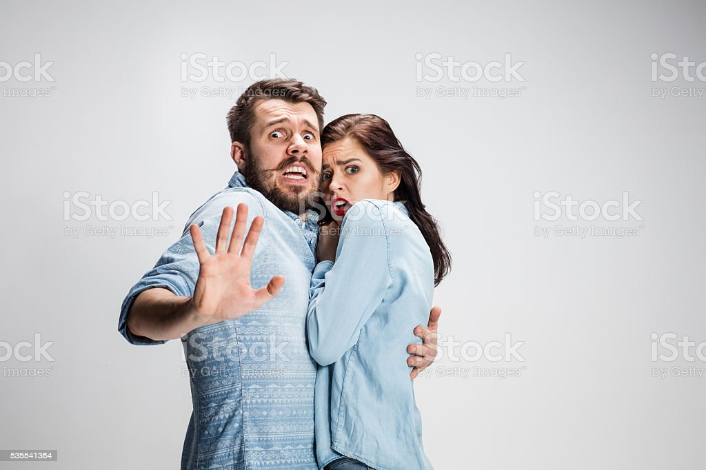 Emotional facial expression wide eyed couple, woman an man looking...