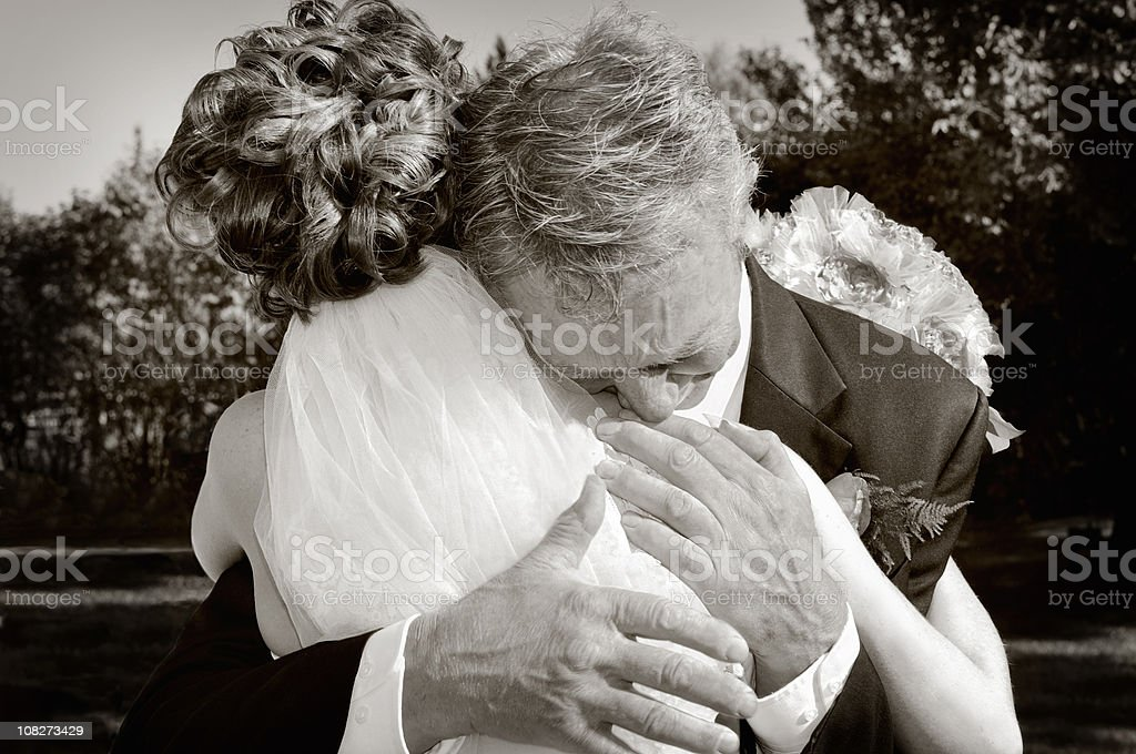 Emotional Father Of The Bride Giving His Daughter A Hug stock photo
