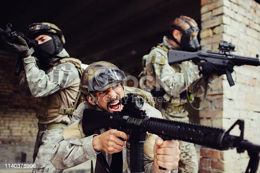 istock Emotional front man is standing outside with his soldiers and screaming. All of them have black rifles. They are dangerous. Guys are ready to fight. 1140378996