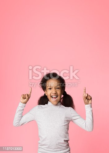 istock Emotional girl pointing fingers up on copy space 1137013300
