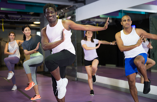 Portrait of excited man dancing during group class in dance center