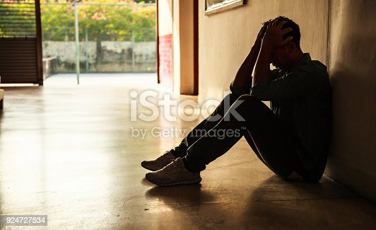 istock Emotional moment: man sitting holding head in hands, stressed sad young male having mental problems, feeling bad, depressed, disappointed, hopeless. Desperate man in the dark corner needing help. 924727534