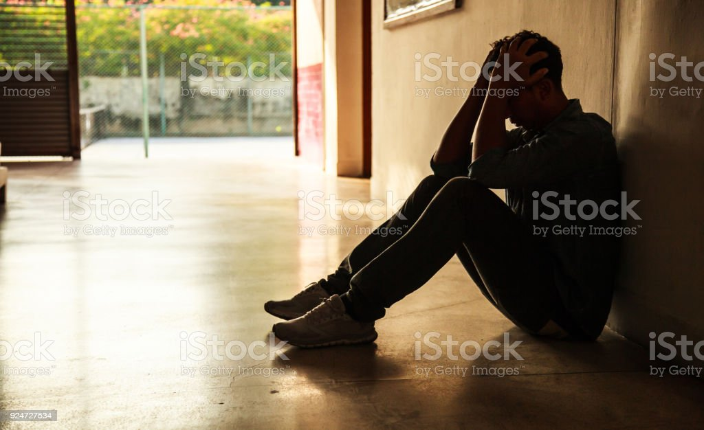 Emotional moment: man sitting holding head in hands, stressed sad young male having mental problems, feeling bad, depressed, disappointed, hopeless. Desperate man in the dark corner needing help. stock photo