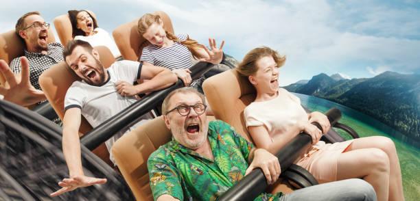 gente emocional en la montaña rusa bajando con praderas sobre el fondo - roller coaster fotografías e imágenes de stock