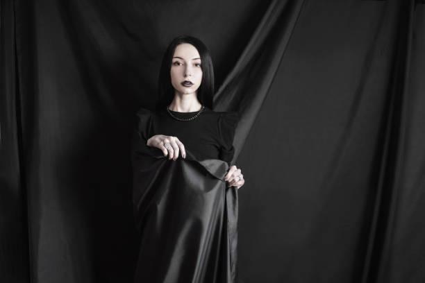 emotionales porträt brünette mädchen mit langen geraden schwarzen haar mit einem natürlichen make-up auf einem schwarzen hintergrund. frau im schwarzen kleid in schwarzes tuch gehüllt. femme fatale-hexe - vampir schminken frau stock-fotos und bilder