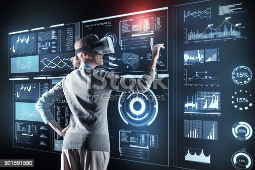 istock Emotional programmer smiling while being in virtual reality glasses 921591590