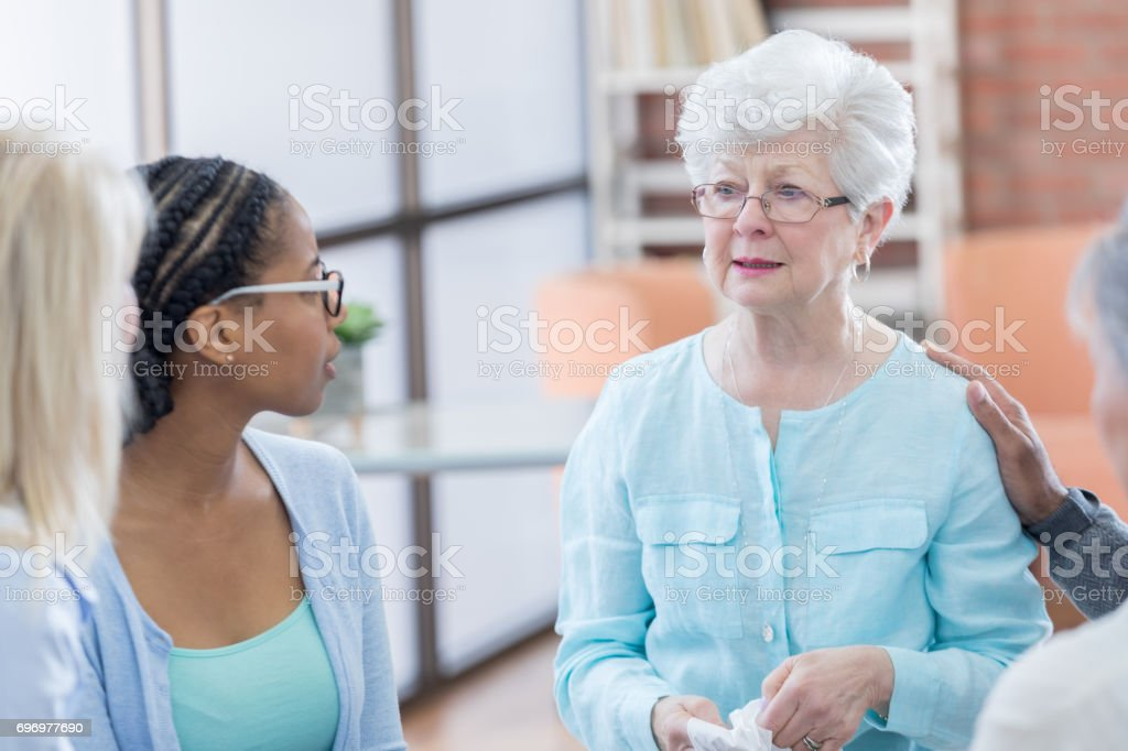Emotional senior woman during group therapy session stock photo