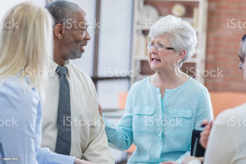 Concerned senior Caucasian woman talks with senior African American...