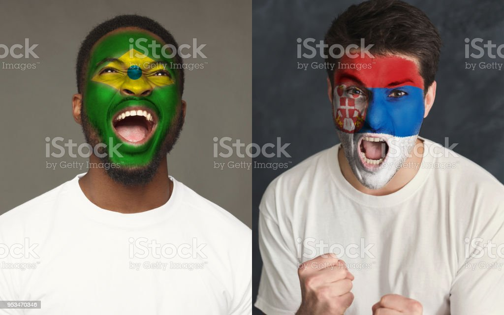 Emotional soccer fans with painted flags on faces stock photo