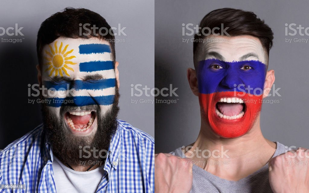 Emotional soccer fans with painted flags on faces - Royalty-free Adult Stock Photo