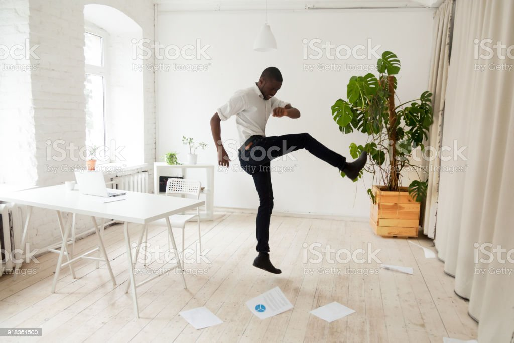 Emotional stressed african-american businessman kicking scattered papers on office floor stock photo