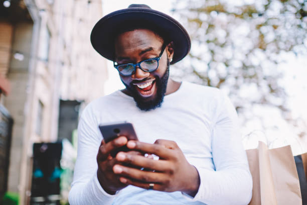 Emotional surprised african american guy with low prices in web store receiving message with promo code,excited dark skinned hipster guy in trendy hat overjoyed with winning online contest on web site stock photo