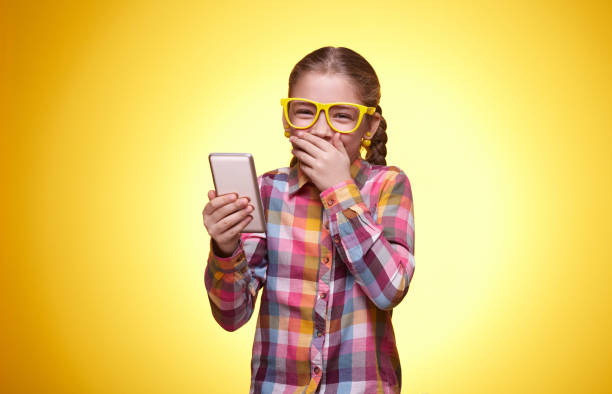 Emotional teen girl with mobile phone on yellow background stock photo