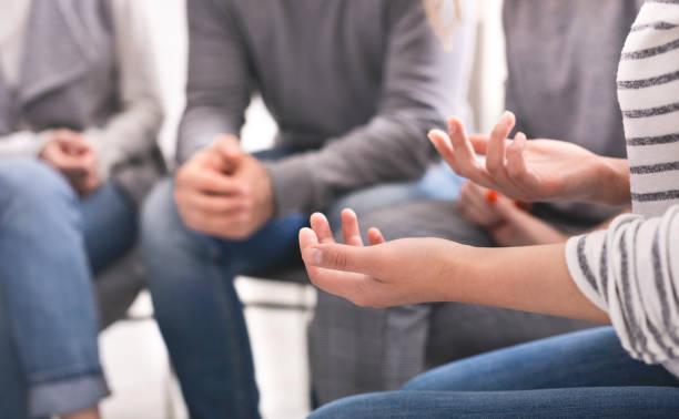 emotionale frau teilt ihre geschichte während support sitzung - gestikulieren stock-fotos und bilder