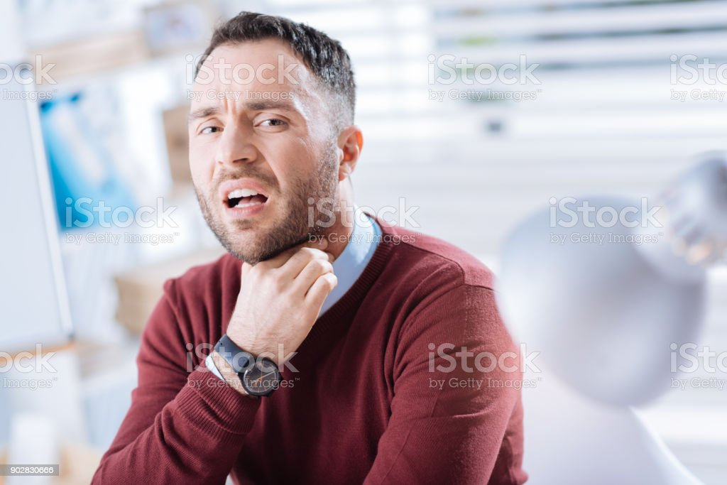Emotional worker touching his neck and having a sore throat stock photo