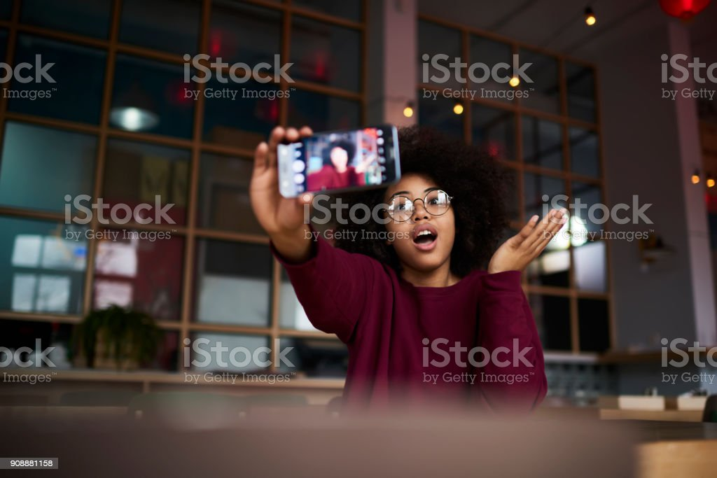 Emotional young afro american girl with curly hair in trendy glasses posing while making photo for updating account picture using modern smartphone camera and wifi access to internet in cafe indoors stock photo