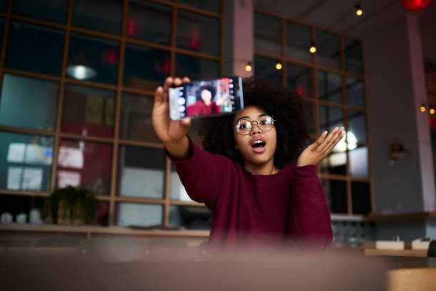 emotional young afro american girl with curly hair in trendy glasses posing while making photo for updating account picture using modern smartphone camera and wifi access to internet in cafe indoors - vlogger stock photos and pictures