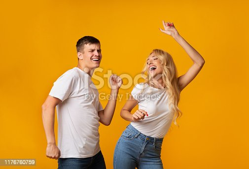 1092709104istockphoto Emotional young couple dancing and laughing on yellow studio background 1176760759