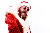 Emotional young man in a Santa Claus costume bespectacled with Christmas toys in a real beard on white background.Copy space.