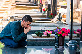 Widower in Black Clothes Kneeling in Front of the Headstone and Praying for the Soul of his Lost Friend. Mid Aged Tired and Sad Man is Sitting Near a Grave in the Cemetery and Mourning Over the Deceased.