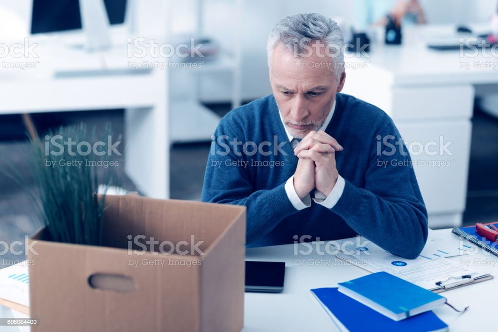 Emotionally washed out man dreaming at work stock photo