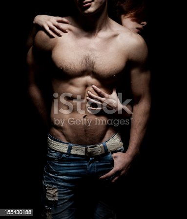 nude torso of man with hands of woman isolated on black
