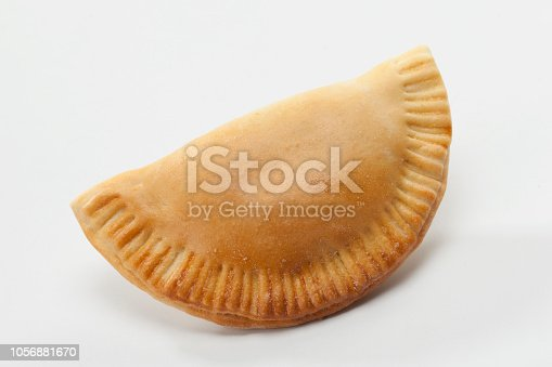 Empanada on white background. Studio shot. An empanada is a type of pasty baked or fried in many countries of the Americas and in Spain. Empanadas are made by folding dough over a stuffing, which may consist of meat, cheese or other ingredients.