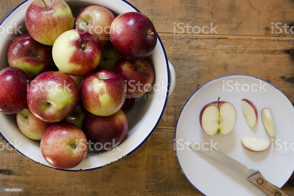 Empire Apples in an Old Colander with One Cut Apple stock photo