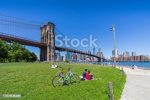 Brooklyn, New York, USA - June 13, 2020:  view of the Brooklyn bridge and Manhattan from Empire Fulton Ferry park during covid-19 pandemic . New Yorkers practicing social distancing.