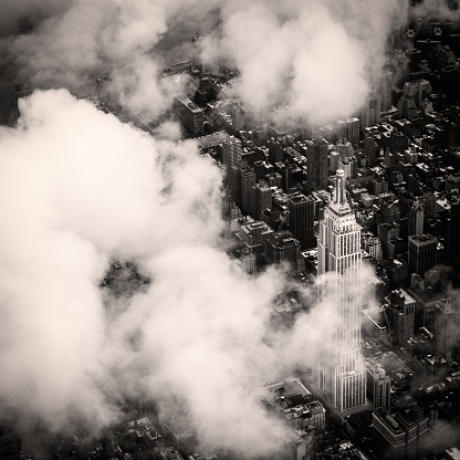 Aerial view of the Empire State Building among clouds, New York.