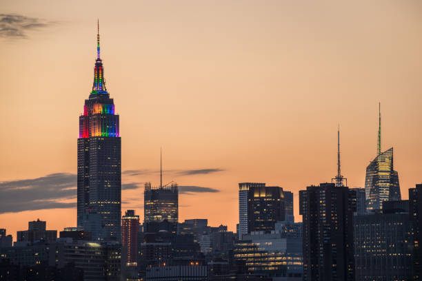 Empire State Building pride sunset A partial skyline of Midtown Manhattan with the Empire State Building displaying Pride colors taken from Brooklyn just before at sunset. gay pride parade stock pictures, royalty-free photos & images