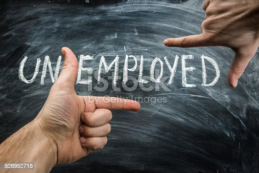 man finger framing only the employed part of the word unemployed written on a blackboard