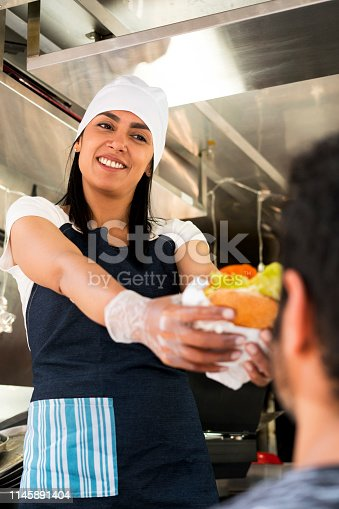 employed woman of food delivers hamburger to male customer while showing a beautiful smile