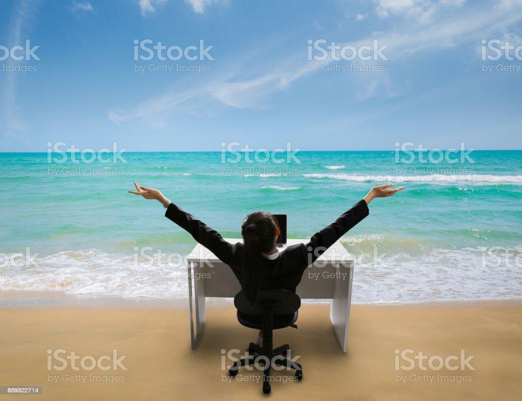 Mitarbeiter freuen uns bei der Arbeit, sie erinnerte sich an ihre Zeit zum Entspannen am Strand im Sommer – Foto