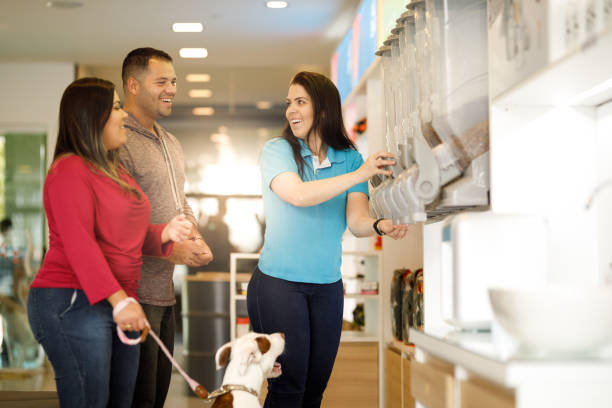 employee assisting customers at pet salon - pet shop and dogs not cats stock pictures, royalty-free photos & images