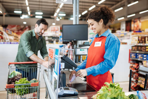Employee at cash register in supermarket, serving the customer stock photo