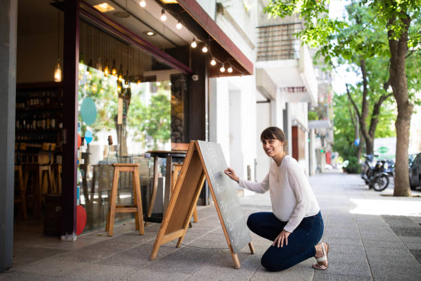 employee at chalkboard outside wine shop - small business owner stock pictures, royalty-free photos & images