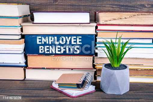 Employee Benefits concept. Books stacked on a wooden table