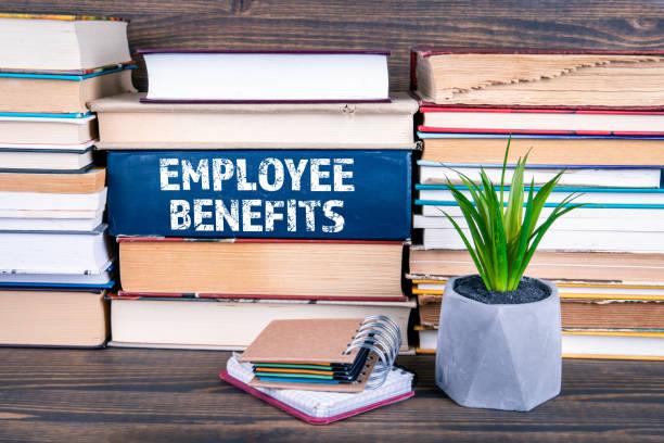 employee benefits concept. books stacked on table - benefits imagens e fotografias de stock
