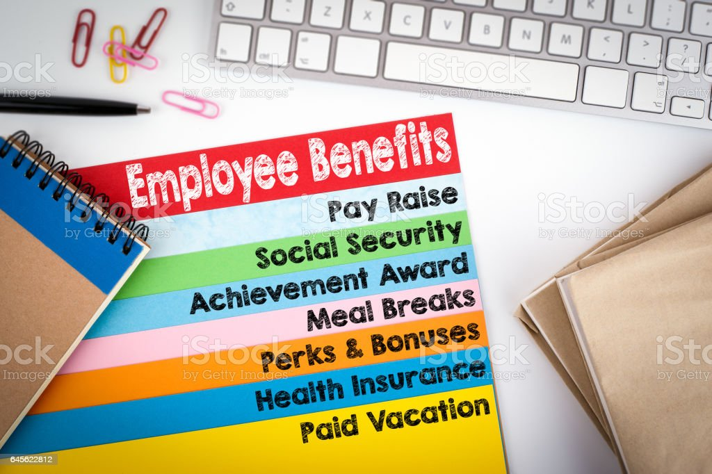 Employee Benefits. Office desk with a computer keyboard and color pages stock photo