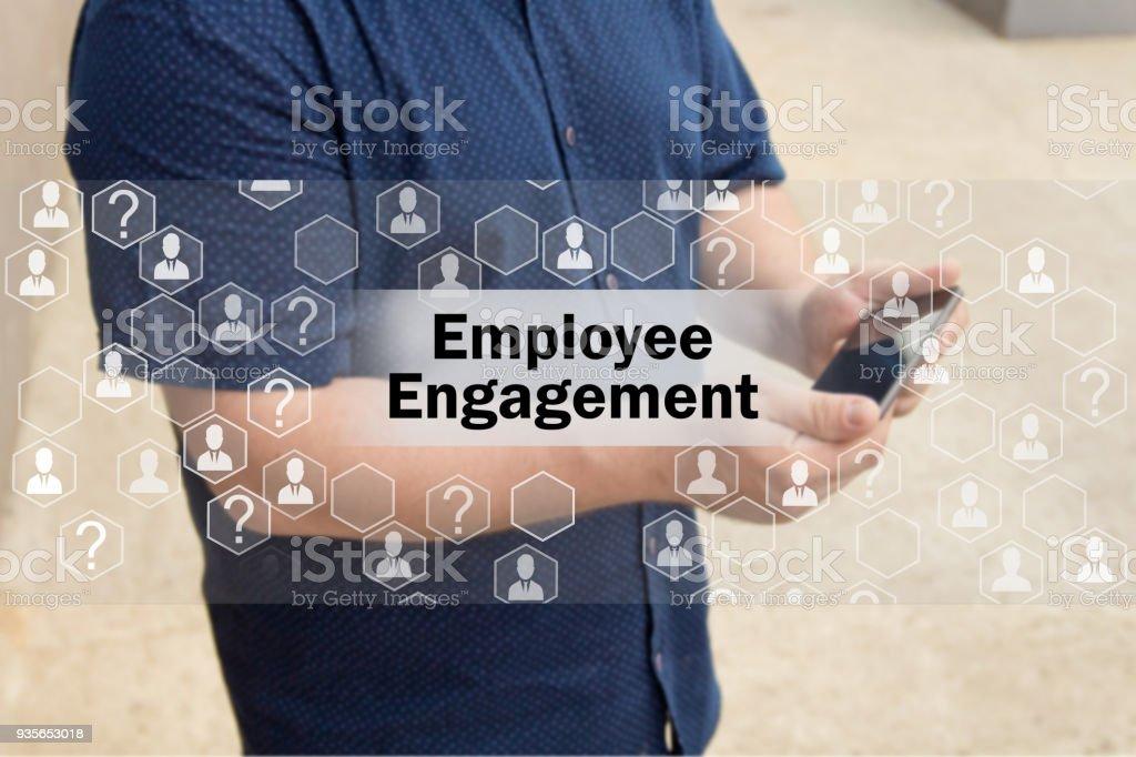 Engajamento dos funcionários na tela de toque com um fundo de borrão do empresário com o telefone. O conceito de engajamento dos funcionários - foto de acervo