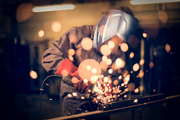 employee grinding steel with sparks - arbeider stockfoto's en -beelden