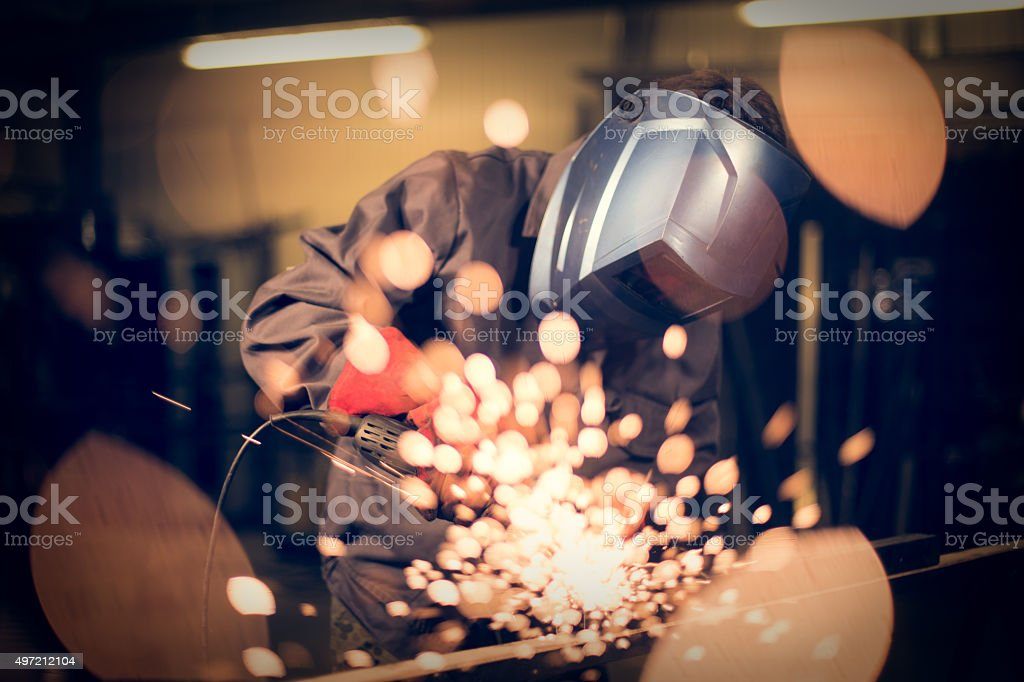 Employee grinding steel with sparks stock photo