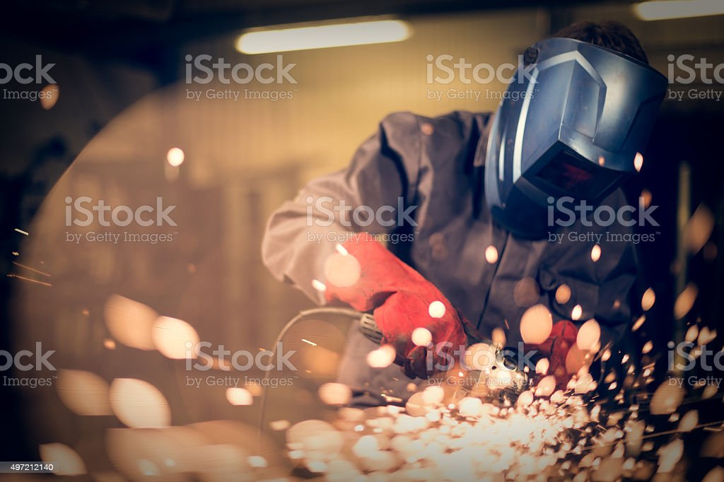 Employee grinding steel with sparks