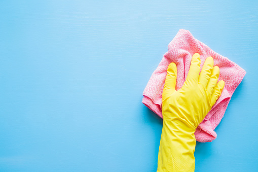 istock Employee hand in rubber protective glove with microfiber rag wiping blue table, wall or floor surface in room, bathroom, kitchen. Early spring or regular cleanup. Commercial cleaning company concept. 938084384