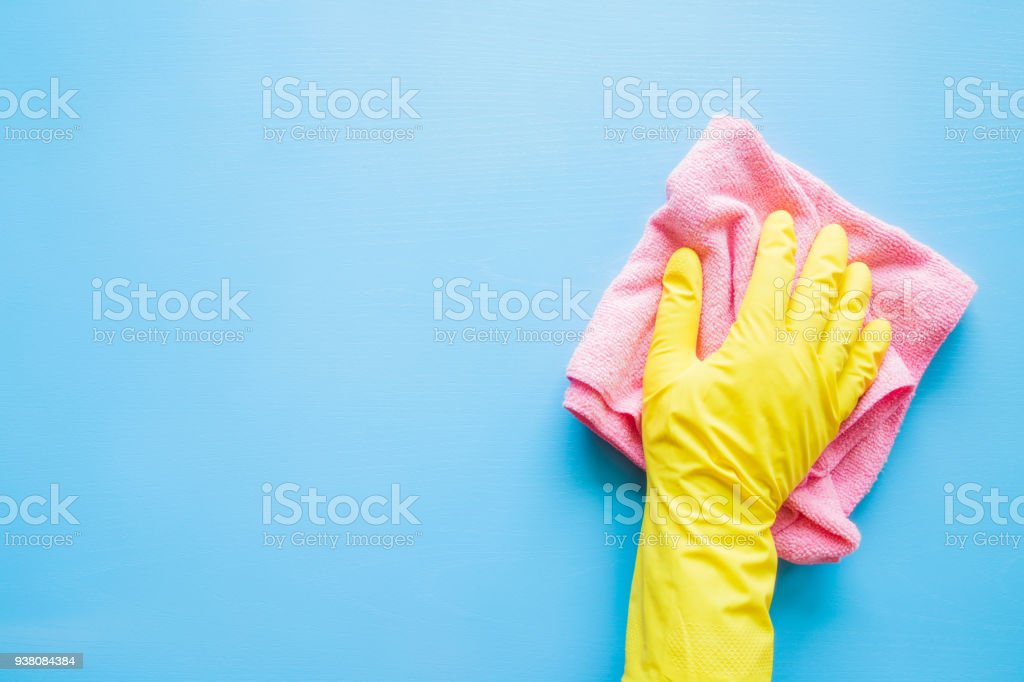 Employee hand in rubber protective glove with microfiber rag wiping blue table, wall or floor surface in room, bathroom, kitchen. Early spring or regular cleanup. Commercial cleaning company concept. stock photo