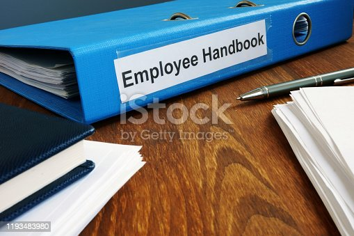 Employee Handbook manual in folder and documents.