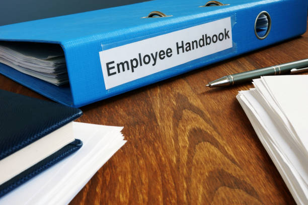 Mitarbeiterhandbuch handbuch in Ordner und Dokumenten. – Foto