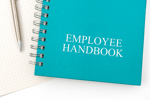 Employee Handbook or manual with a pen and paper on a white table in an office - personnel management policy, explains business goals, results, defines personnel practices